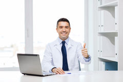 Smiling doctor showing thumbs up in medical office Royalty Free Stock Image