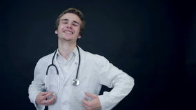 Smiling Doctor showing thumbs up, standing on a black background putting on a stethoscope. Packshot. stock footage