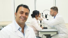 A smiling doctor sits while on the background another doctor examines the patient. The doctor is sitting in the foreground. He smiles and looks very friendly. In Stock Photos