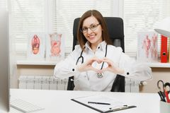 Smiling female doctor sitting at desk, showing shape heart with hands, working with medical documents in light office in royalty free stock photography