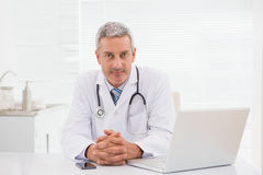 Smiling doctor sitting at his desk Royalty Free Stock Image
