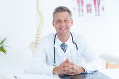 Smiling doctor sitting at his desk Stock Images