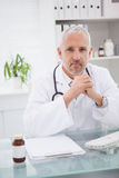 Smiling doctor sitting at his desk Stock Photography
