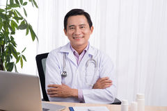 Smiling doctor sitting at his desk in medical office writing pre Royalty Free Stock Photo