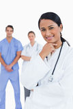 Smiling doctor with staff behind her Stock Images