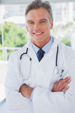 Smiling doctor standing with arms crossed Stock Photos