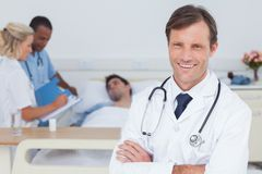 Smiling doctor standing and looking at the camera royalty free stock photography