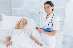 Smiling doctor standing next to her patient. In hospital room Stock Photography