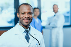 Smiling doctor with stethoscope with colleagues behind in clinic Royalty Free Stock Images