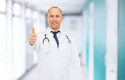 Smiling doctor with stethoscope showing thumbs up Stock Images