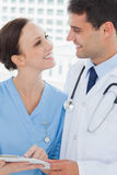 Smiling doctor and surgeon attractively looking at each other Royalty Free Stock Photos