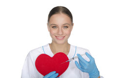 Smiling doctor with a syringe pricks heart symbol. Smiling doctor with a syringe pricks red heart symbol Stock Images