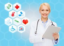 Smiling doctor with tablet pc and medical symbols Stock Images