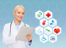 Smiling doctor with tablet pc and medical symbols Stock Photo