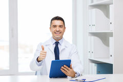 Smiling doctor with tablet pc showing thumbs up Stock Photography