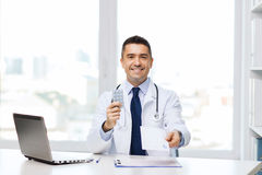 Smiling doctor with tablets and laptop in office Stock Photo