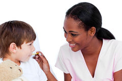 Smiling doctor taking child's temperature stock photography