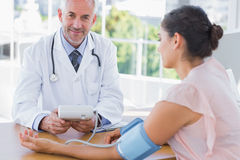 Smiling doctor taking the heartbeat of a patient Royalty Free Stock Photography