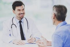 Smiling Doctor Talking with Patient at his Office. Stock Images