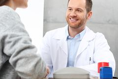 Smiling doctor talking with a patient. stock images