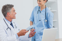 Smiling doctor talking to a colleague Stock Images