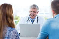 Smiling doctor talking to happy couple Royalty Free Stock Images