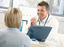 Smiling doctor talking to patient. At office desk royalty free stock photo