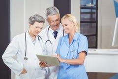 Smiling doctor team using digital tablet Royalty Free Stock Image
