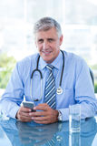 Smiling doctor texting with his mobile phone Royalty Free Stock Image