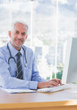 Smiling doctor typing on his computer Stock Image