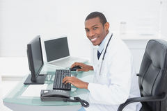 Smiling doctor using computer at medical office Royalty Free Stock Photos
