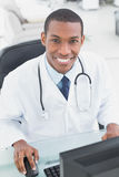 Smiling doctor using computer at medical office Royalty Free Stock Photo