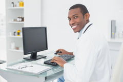 Smiling doctor using computer at medical office Stock Image