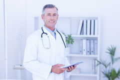 Smiling doctor using digital tablet Royalty Free Stock Photo