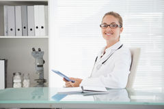 Smiling doctor using her tablet Stock Photo