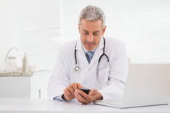 Smiling doctor using his phone Royalty Free Stock Images