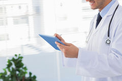 Smiling doctor using his tablet pc Royalty Free Stock Images