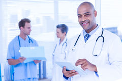 Smiling doctor using his tablet Stock Photos