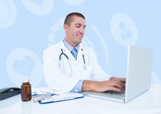 Smiling doctor using laptop at desk Royalty Free Stock Image