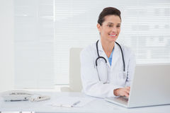 Smiling doctor using laptop Stock Images