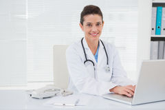 Smiling doctor using laptop Royalty Free Stock Photography