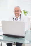 Smiling doctor using laptop Royalty Free Stock Images