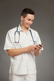 Smiling doctor using mobile phone Stock Photography