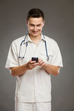 Smiling doctor using mobile phone Stock Image