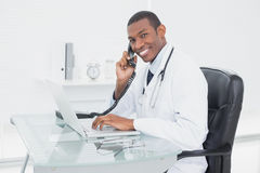 Smiling doctor using phone and laptop at medical office Stock Image