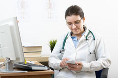 Smiling doctor using smartphone Royalty Free Stock Photography