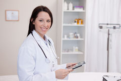 Smiling doctor using a tablet computer Royalty Free Stock Images