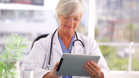 Smiling doctor using a tablet computer. In a bright office stock footage