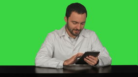 Smiling doctor using tablet on a Green Screen. Chroma Key. Professional shot on BMCC RAW fith high dynamic range. You can use it e.g in your commercial video stock video