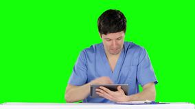 Smiling doctor using a tablet. Green screen. Smiling doctor using a tablet, doctor with tablet computer, doctor working at the computer, workflow in the clinic stock video